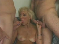 granny sucks and plays with two cocks