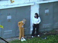 Two office girls pee quietly in a yard